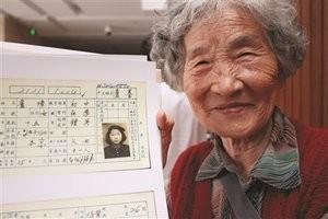 Xu Zhang, 84, shows her teen photo on her family's household registration card [Yangtze Evening Post/Zhang Ke]